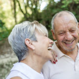 Older couple laughing in the field