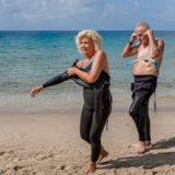 Retired couple putting on their wetsuits on the beach to go swimming.