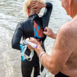 Older man helping his wife put on a wetsuit on the beach to go for a swim