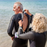 Older woman helping her husband to put on his wetsuit on the beach for a swimming trip