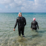 Retired couple on the beach dressed in wetsuits going for a swim