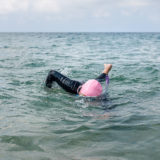 Woman in wetsuit with snorkeling goggles and pink swim cap swimming in the sea.