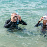Retired couple taking off their snorkeling goggles after swimming in the sea.