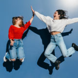two friends a blonde and a brunette happily jumping in front of a blue wall