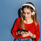 Young blonde girl with long hair, chatting and listening to cell phone music with headphones leaning against a blue wall.