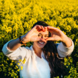 Young girl making the symbol of love in a field of rapeseed at sunset.