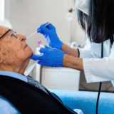 Nurse performing covid test on an elderly person at home.