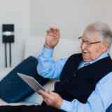 Elderly man video conferencing with a digital tablet