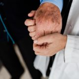 Woman's hand affectionately holding the hand of an older man.