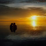 Young couple on the beach kissing during sunset