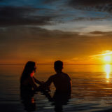 Young couple on the beach watching the sunset
