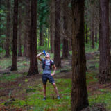 Sportsman mountain runner drinking water in the forest full of trees.